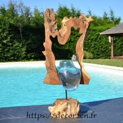Vase en verre soufflé en fusion dans le trou du rondin de teck